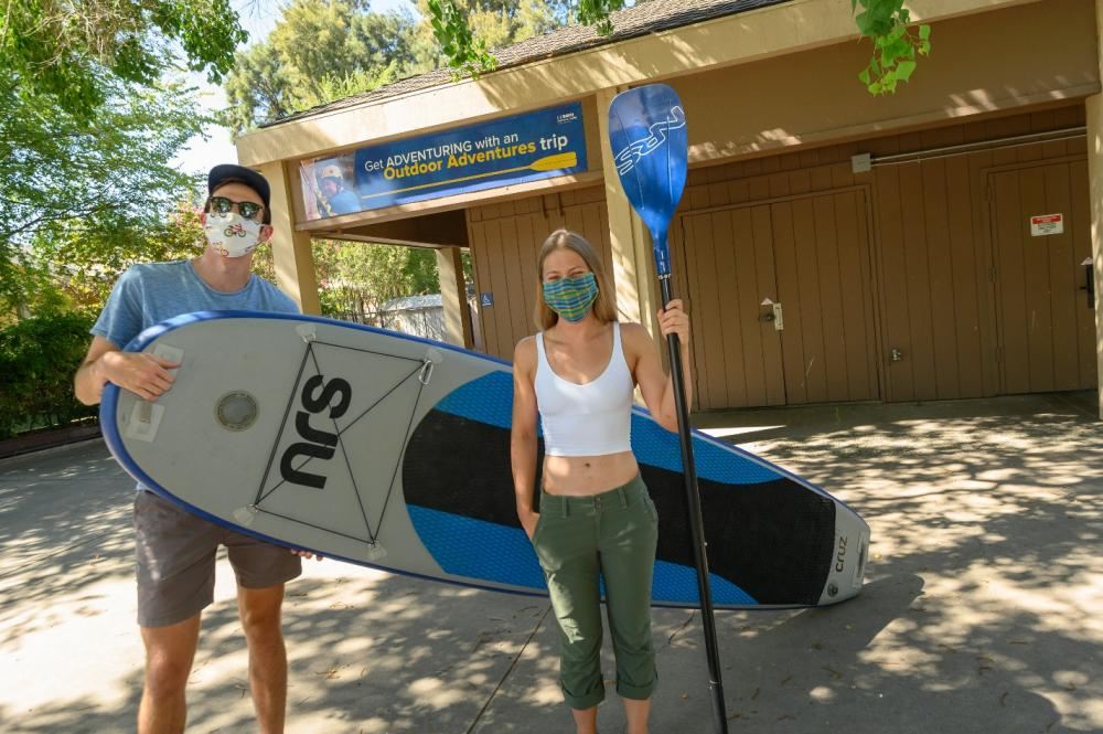 Two students stand outside Outdoor Adventures, holding a paddleboard and paddle.