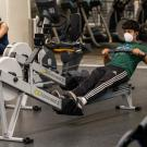 A student, wearing a mask, uses the rowing machine at the ARC